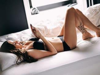 девушка на постели с телефоном